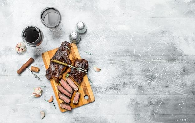 Стейк из говядины с красным вином. на деревенской поверхности.