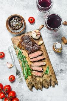 Стейк из говядины с красным вином. на деревенском столе.