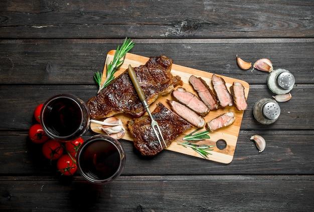레드 와인으로 구운 쇠고기 스테이크. 나무 테이블에.