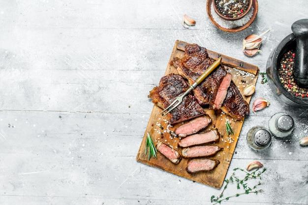 Стейк из говядины с розмарином и специями. на деревенской поверхности.