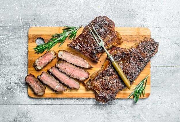 Стейк из говядины с розмарином и специями. на деревенском столе.