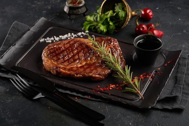 로즈마리와 어두운 배경에 향신료와 구운 쇠고기 스테이크