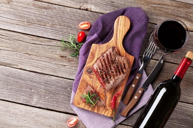 木製のテーブルにローズマリー、塩、コショウ、ワインボトルを添えたビーフステーキのグリル。コピースペースのある上面図
