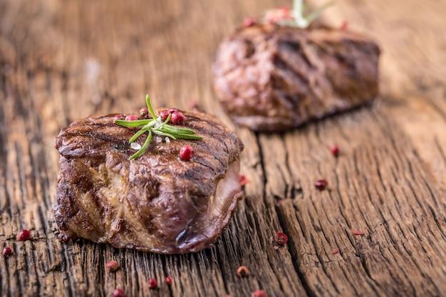 Стейк из говядины с розмарином, солью и перцем на старой разделочной доске. стейк из говяжьей вырезки.