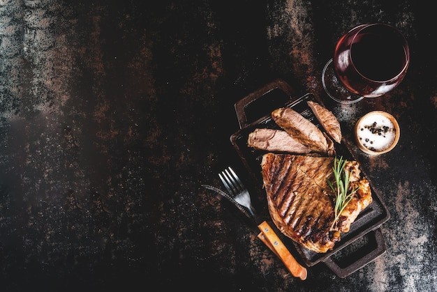 Grilled beef steak with spices on grill pan board, with and red wine glass.  copyspace top view