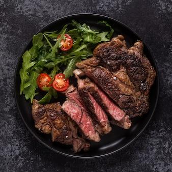 검은 접시에 향신료를 곁들인 구운 쇠고기 스테이크, 위쪽 전망.