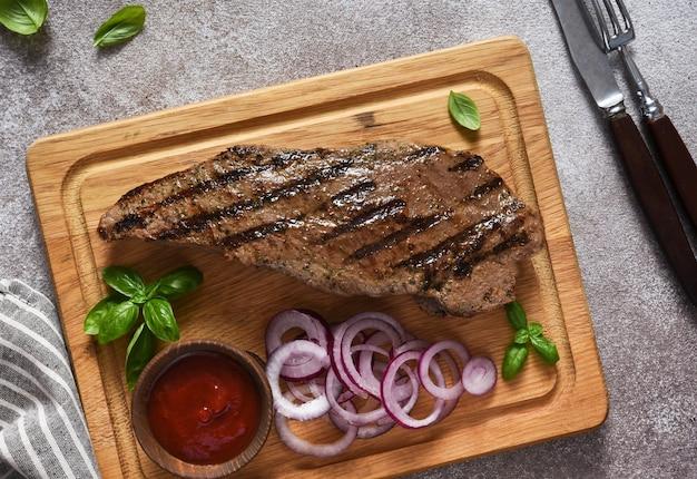 나무 판자에 토마토 소스와 절인 붉은 양파를 곁들인 구운 쇠고기 스테이크. 위에서 볼 수 있습니다.