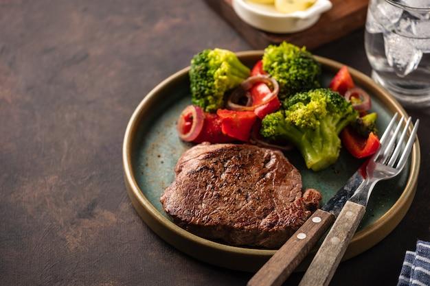 Стейк из говядины на гриле с овощами. мясо с жареным болгарским перцем, брокколи и луком