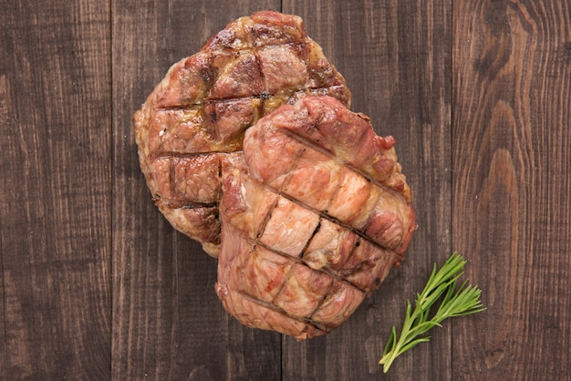 Grilled beef steak on a wooden background