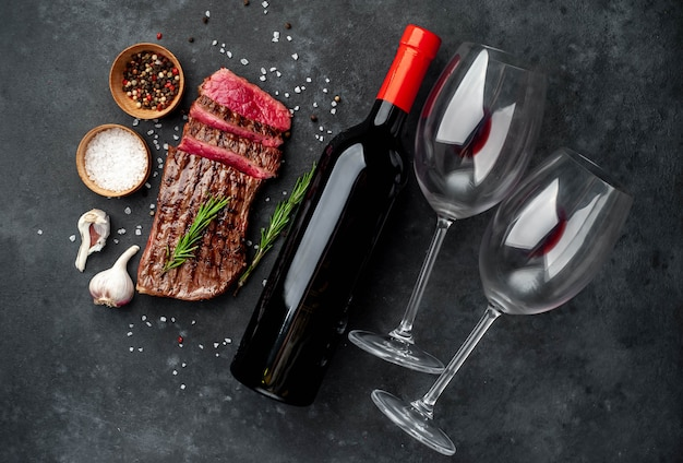 Grilled beef steak on a wooden board and a bottle of wine and glasses on a stone background
