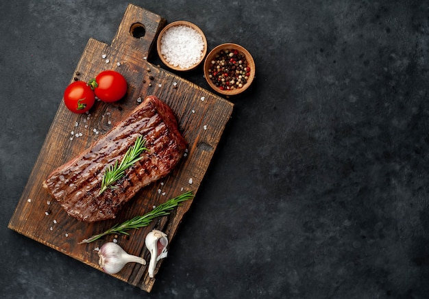 Grilled beef steak on a wooden board with spices on a stone background with copy space for your text
