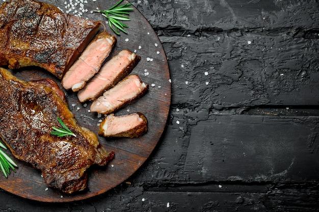 Стейки из говядины на разделочной доске. на черной деревенской поверхности.
