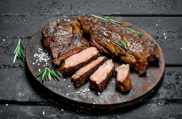 Стейки из говядины на разделочной доске. на черном деревенском столе.