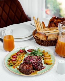 Grilled beef steaks topped with tomato sauce, served with potato, ketchup and salad