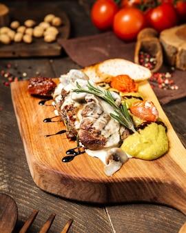 Стейки из говядины на гриле со сливочным соусом с овощами на деревянной доске