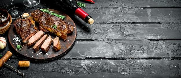 허브와 레드 와인으로 구운 쇠고기 스테이크. 검은 소박한 배경.