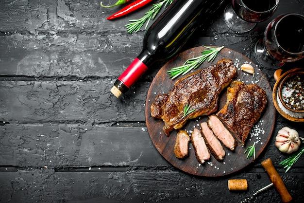 Стейки из говядины на гриле с зеленью и красным вином. на черном деревенском фоне.