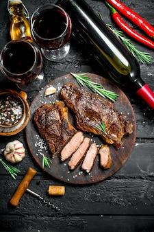 Стейки из говядины на гриле с зеленью и красным вином. на черном деревенском столе.