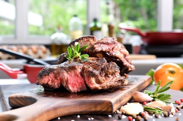 부엌에 있는 나무 커팅 보드에 향신료를 곁들인 구운 쇠고기 스테이크