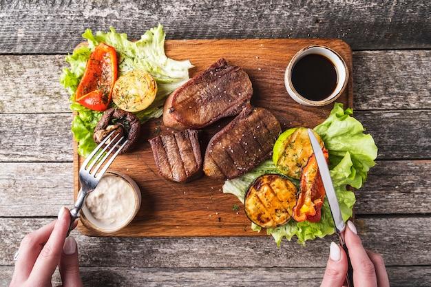 木の板に野菜とソースを添えた牛タンのグリル。上面図