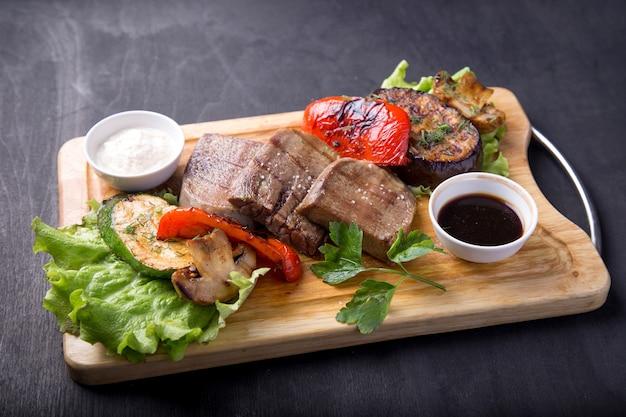 Жареный говяжий язык с овощами и соусом на деревянной доске