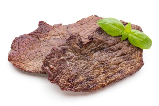 Жареные био стейки из говядины со специями, изолированные на белом.