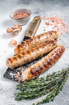 식칼에 구운 bockwurst와 bratwurst 고기 소시지. 흰 바탕. 평면도.