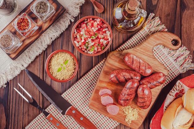 パン、サラダ、ファロファ、食材を使った木の板で焼いたブラジルソーセージ