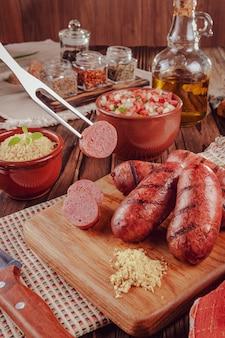 木の板にサラダ、ファロファ、材料を添えたブラジルソーセージのグリル