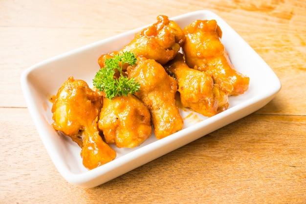 Жареные крылышки буйвола в белой тарелке
