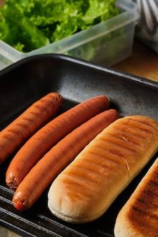 구운 빵과 소시지. 핫도그 재료. 핫도그 요리 과정. 패스트 푸드.