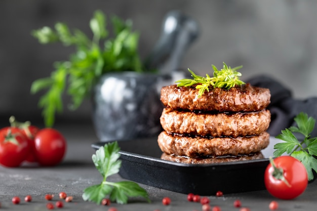 Grilled burger patties with herbs, spices on a dark
