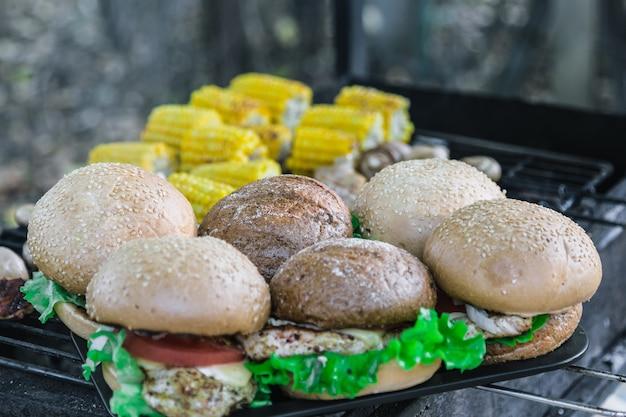 Жареные гамбургеры на открытом воздухе. с сыром, луком, салатом, помидором