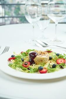 Жареный сыр камамбер с яблоками, клубникой и черникой в белой тарелке на белой тарелке