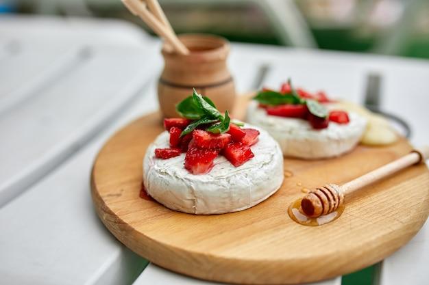 Сыр камамбер на гриле с клубникой, медом и листьями базилика, деликатесы.