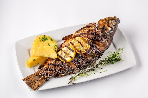 Grilled carp fish with rosemary potatoes and lemon