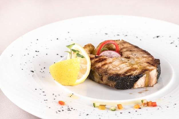 Grilled carp,  served with lemon and decorated with radish and fresh leafs,  light backgro