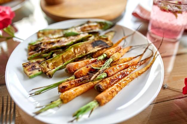 夕食のテーブルの皿にニンジンとズッキーニのグリル、自宅のパーティーの屋外テーブルで前菜のバラエティを提供しています。