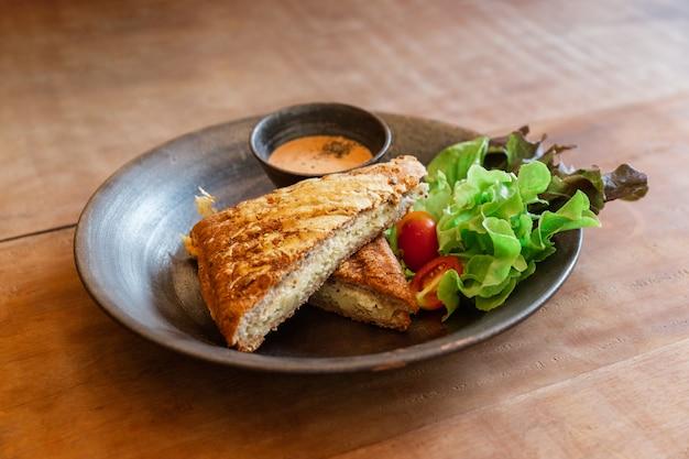 セラミックプレートに千島ソースとグリーンオークとトマトを含むサラダを添えたグリルチーズサンドイッチ。