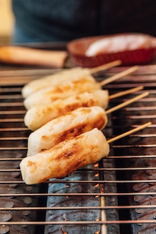 Grilled cheese stick on gas griller stove, street food at ximending in taiwan, taipei.