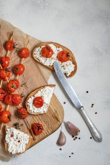 Жареные помидоры черри на шпажках, на бумаге для выпечки. итальянская брускетта с помидорами и сыром
