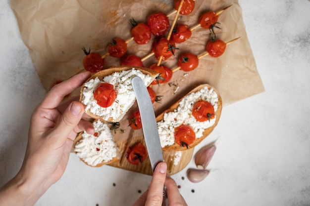 Жареные помидоры черри на шпажках с брускеттой с помидорами и сыром, вид сверху.