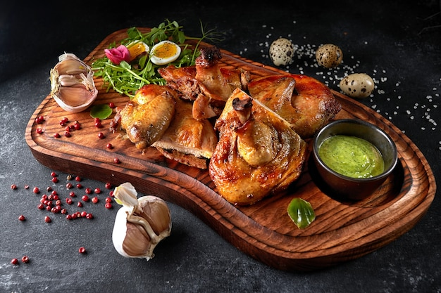 Grilled chick with herbs and sauce on a wooden board on a black background