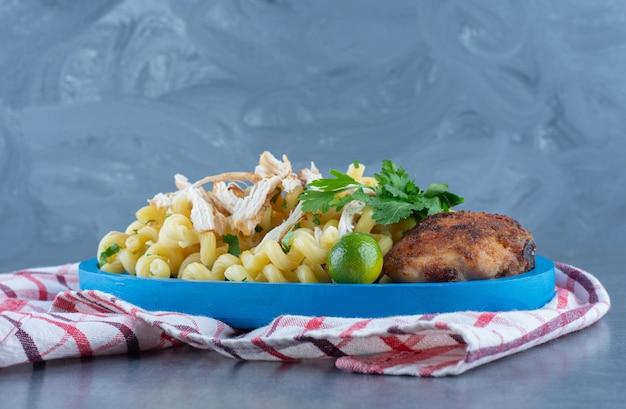 Жареный цыпленок и макароны на синей тарелке.