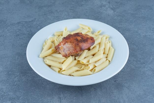 Жареный цыпленок и макаронные изделия пенне в белом шаре.