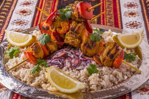 Кебаб из курицы и овощей на гриле, подается с рисом и салатом на подносе