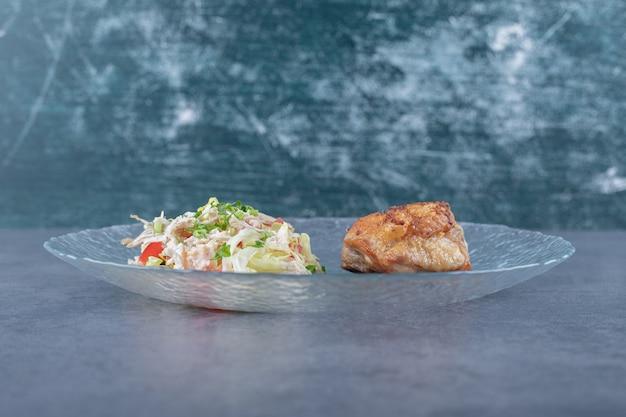 Жареный цыпленок и овощной салат на стеклянной тарелке.