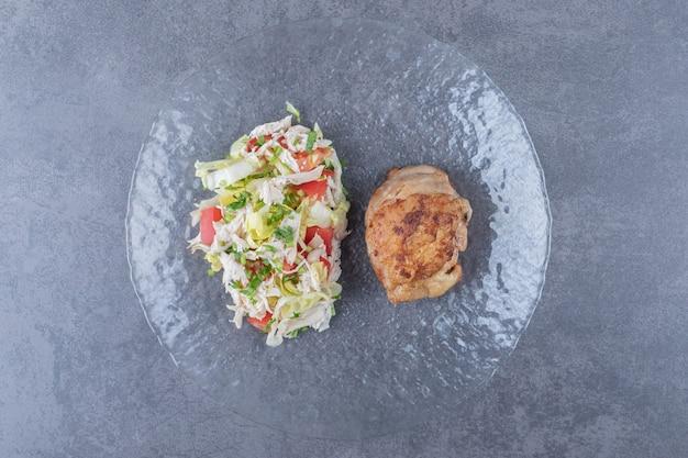 ガラス板にグリルした鶏肉と野菜のサラダ。