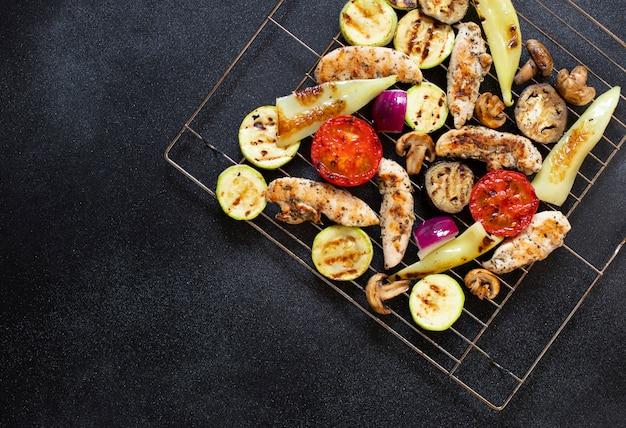구운 닭고기와 야채, 토마토, 고추, 양파, 가지와 호박. 건강한 다이어트 음식. 건강한 저녁. 저지방 함량. 상위 뷰, 검정색 배경, 복사 공간