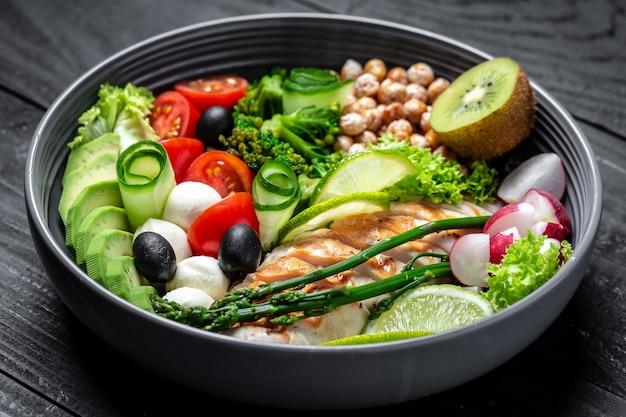 구운 닭고기, 아보카도, 아스파라거스, 병아리 콩, 브로콜리, 무, 닭고기, 오이, 토마토, 올리브, 어두운 배경에 모짜렐라 부처님 그릇, 평면도. 맛있는 균형 잡힌 음식 개념